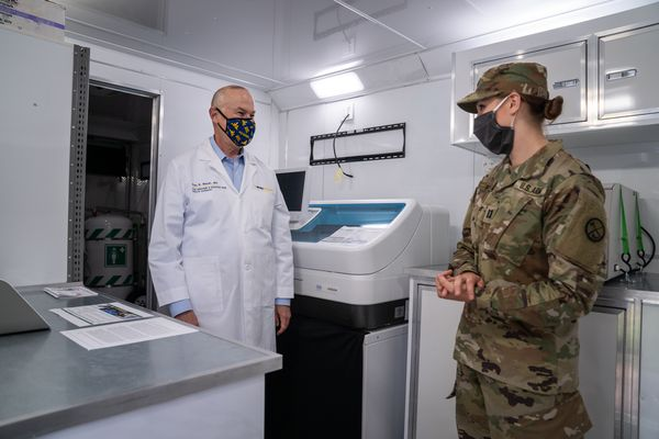young woman in mask and military clothes in conversation with doctor in lab coat